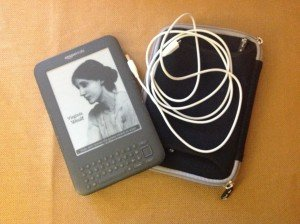 A gently used kindle with the keyboard, a black foamy case and a connection cord