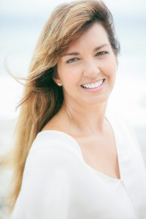 Jane has long brown hair with lots of blond highlights, probably from the sun, She smiling and the bright white of her smile matches her white v-neck top. She's outside, the wind is blowing her hair and she's at the beach. (Jealous!)